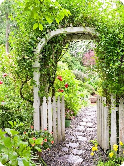 Stone path through white picket fence and arbor
