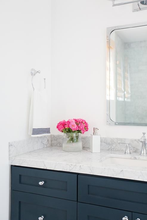 Fabulous white and navy bathroom features a navy vanity painted Benjamin Moore Hale Navy topped with carrera marble under a Restoration Hardware Industrial Rivet Medicine Cabinet illuminated by a three light sconce.