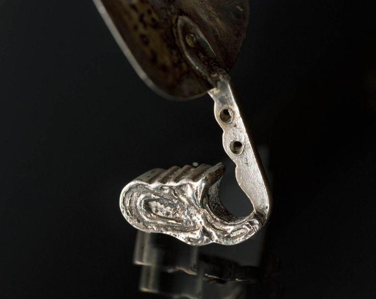 Zilveren oorijzer, gedragen door vrouw of meisje van het eiland Urk. Het oorijzer is gemaakt in 1892. De uiteinden van het Urker oorijzer buigen halverwege sterk naar voren. Ze drukken zodoende in de wang van de draagster. #Urk