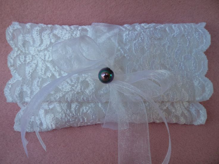 Envelope favour made of white lace and decorated with white organtza ribbon and a dark colour pearl.