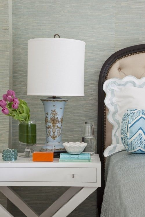 A well styled nightstand with textured wallpaper
