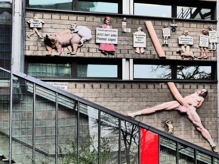 """Wandfüllende Skulptur """"Friede sei mit dir"""" von Peter Lenk am Verlagshaus der Tageszeitung taz in der Rudi-Dutschke-Straße, Kreuzberg. Das Bild zeigt den ehemaligen Chefredakteur der """"Bild"""", Kai Diekmann, mit einem riesigen Penis."""