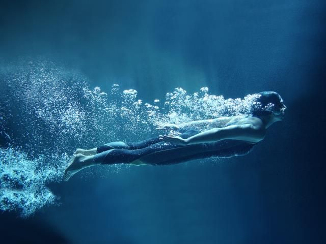Woman swimming in dark pool shutterstock