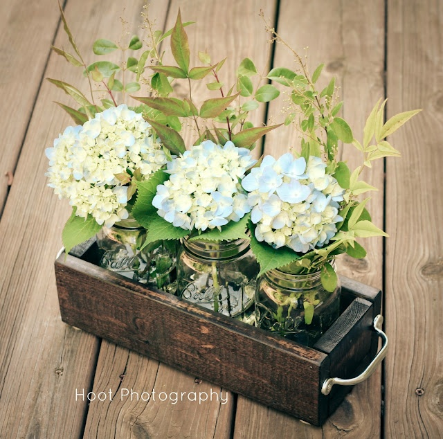 Flowers and greenery in  a container holding mason jars from adiamondinthestuff.blogspot.ca