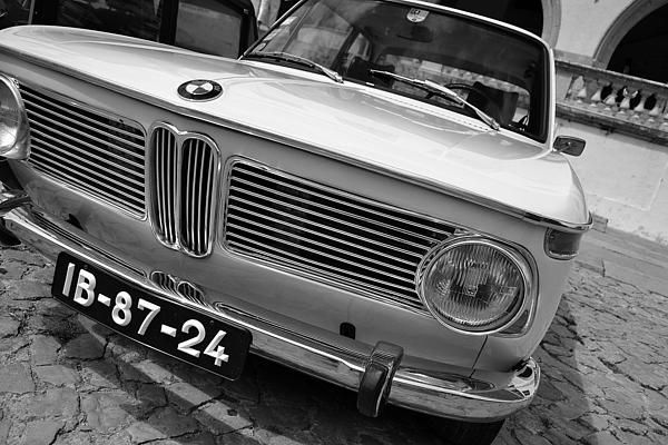My first sale on Fineartamerica!    The BMW New Class (German: Neue Klasse) was a line of compact sedans and coupes produced by German automaker BMW starting with the 1962 1500 and continuing through the last 2002s in 1977.    Powered by BMW's celebrated four-cylinder M10 engine, the New Class models featured a fully independent suspension, MacPherson struts in front, and front disc brakes. Initially a family of four-door sedans and two-door coupes, the New Class line was broadened to…