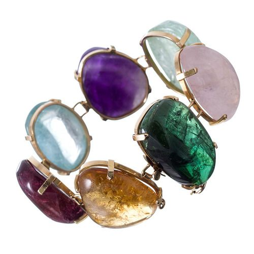 Organic Chic Large Cabochon Gemstone Bracelet. Seven large cabochon gemstones, set in 18k yellow gold form a chic organic statement piece of genuine substance. The stones weigh an approximate 550 carats and are all of slightly differing shapes and proportions.