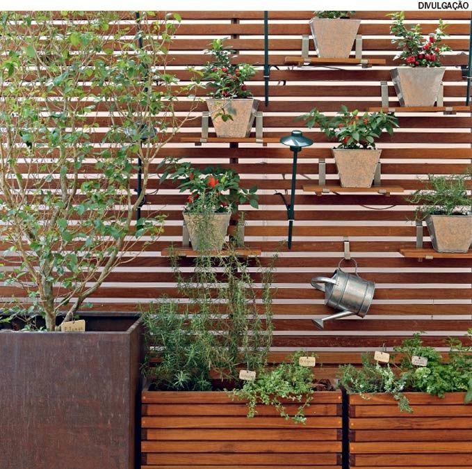 O biombo de ripas de madeira foi a solução desenvolvida pela arquiteta Ana Paula Souza para ganhar mais espaço para as ervas. Detalhe: as alças de aço inox que apoiam as tábuas de madeira aceitam mudanças de posição.
