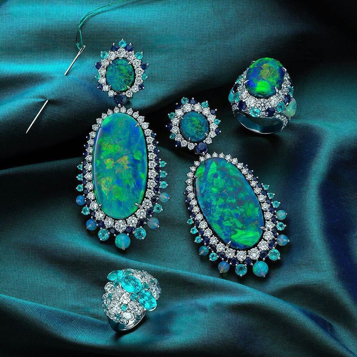 @davidmorrisjeweller. Seen here are our 74.17ct black opal earrings alongside two of our most unique rings, an incredibly rare 16.65ct black opal ring with twist sapphires, tsavorites and white round diamonds set in 18ct white gold in addition to our oval Paraiba tourmaline and oval white diamond ring also set in 18t white gold.