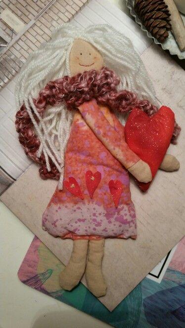 Bambola in stoffa con cuori, fatta a mano. I capelli e la sciarpa sono realizzati in lana.