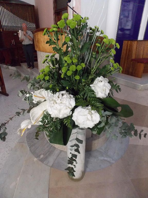A pretty arrangement made of White Hydrangeas and white Amaryllis supported by Chrysanthemum buds and other green foliage. This arrangement provided an attractive focus point next to the reading stand in the church.