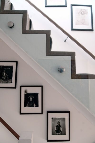timber treads exposed on side of stair with carpeted treads and side fixed glass balustrades