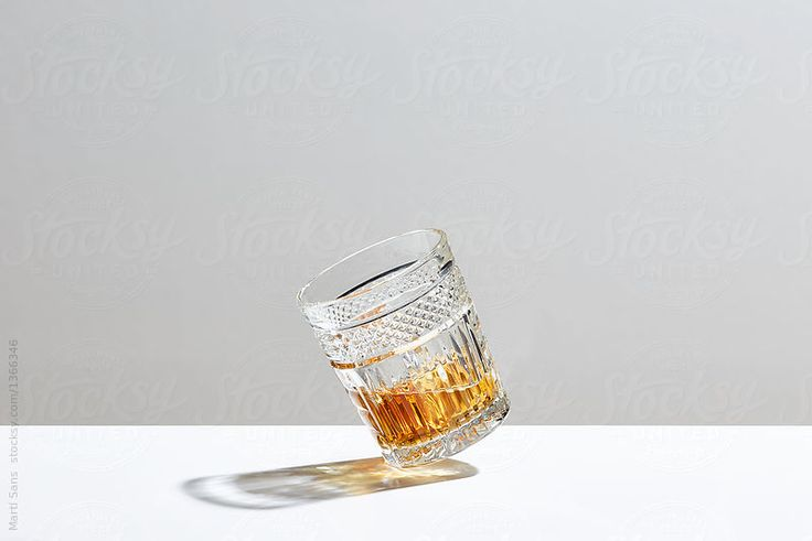 Glass of whiskey falling down on white background.