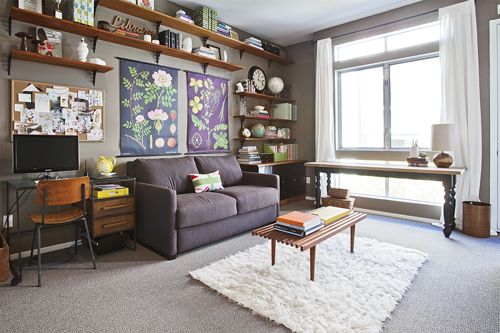 Floor to ceiling open shelving around the living room couch