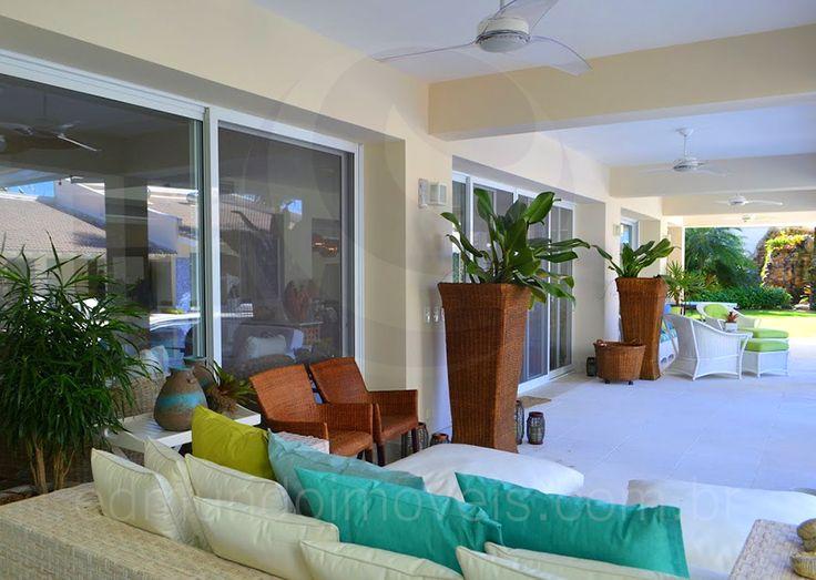 Sob o alpendre, dois lounges compostos por vasos altos e móveis de fibra natural com estofados em tons de verde e turquesa recebem os moradores para o descanso nas tardes ensolaradas.