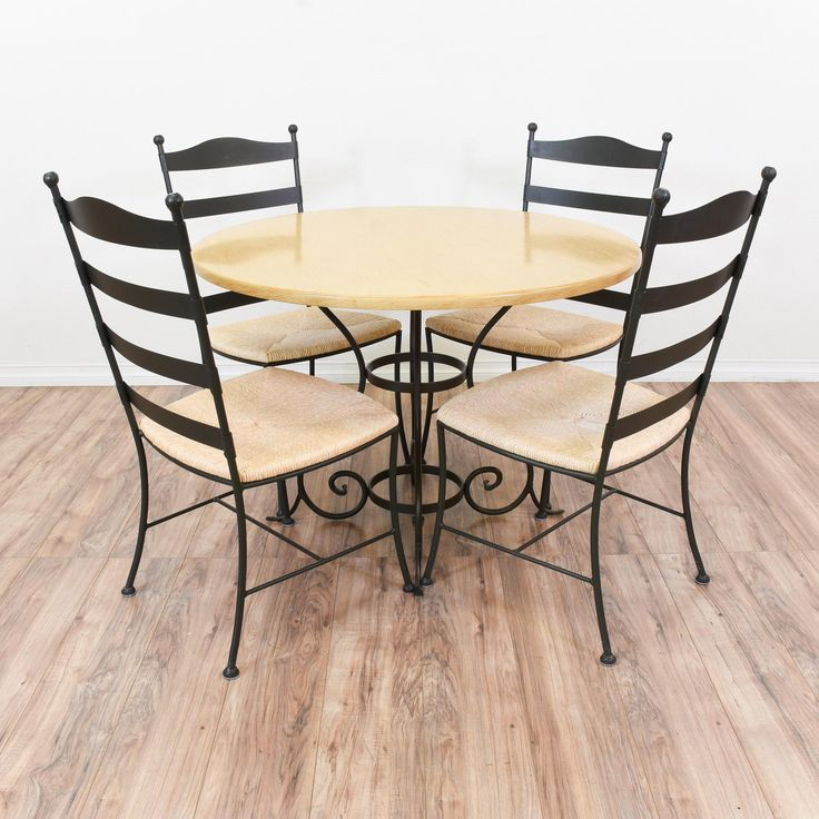 This outdoor dining set is featured in a wrought iron with a shiny black finish. This dining set is in great condition with tall ladder back chairs, woven rush seats and a round dining table with a swirl pedestal base. Perfect for an outdoor patio or porch! #mediterranean #tables #diningset #sandiegovintage #vintagefurniture