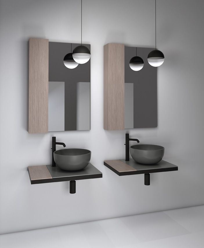 Multiplo modular bathroom collection by CIELO, made up of a pair of Cielo countertop basins on two ceramic tops, in the Cemento finish. The accessory shelf and wall units are natural oak, and the two mirrors render the entire space highly dynamic. The base structure is matte black lacquer. #bathroomdesign #ceramic #interiordesign #HandMadeinItaly #Inspiration #washbasin