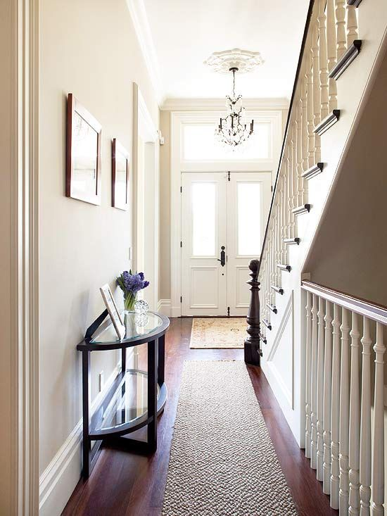 Home's Central Hub     The main-level hall is rich with Victorian architectural details -- beautiful trim and the crafted stairway railings. From here, the homeowners are able to access parlors a powder room, the dining room, kitchen, family room, and stairs to the upper level. A charming light fixture hangs in the entry and pays homage to the period-style of the home