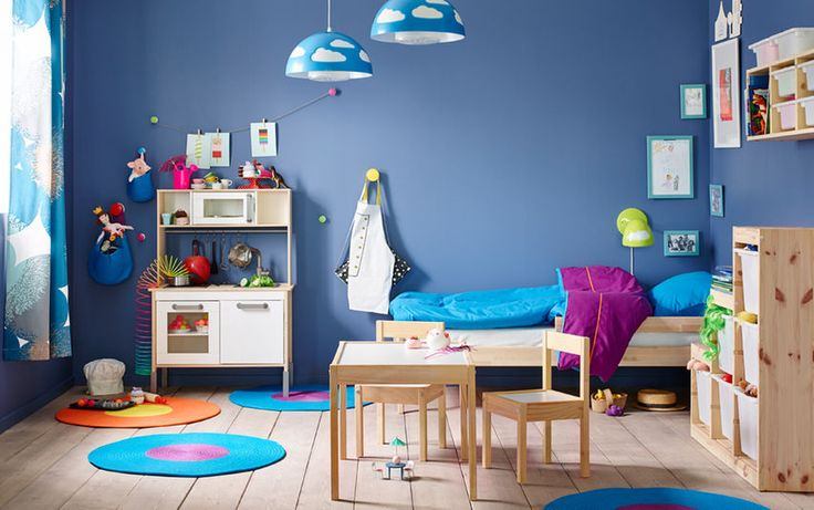 A small children's bedroom furnished with a pine bed with bedlinen in turquoise and lilac. Shown together with a play kitchen and a pine table with two chairs.