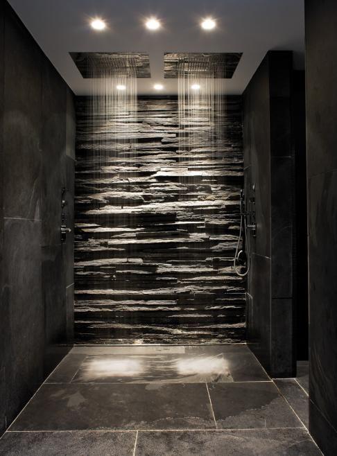 Un moderno baño, con sus paredes cubiertas de pizarra y mármol.