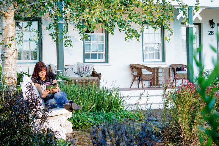 A relaxed guest reads in the gardens at Tsitsikamma Village Inn.