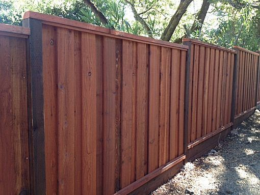 Redwood privacy fence with top cap and pressure treated posts.  Could use either 1x6 or 1x8 boards for this classic look!