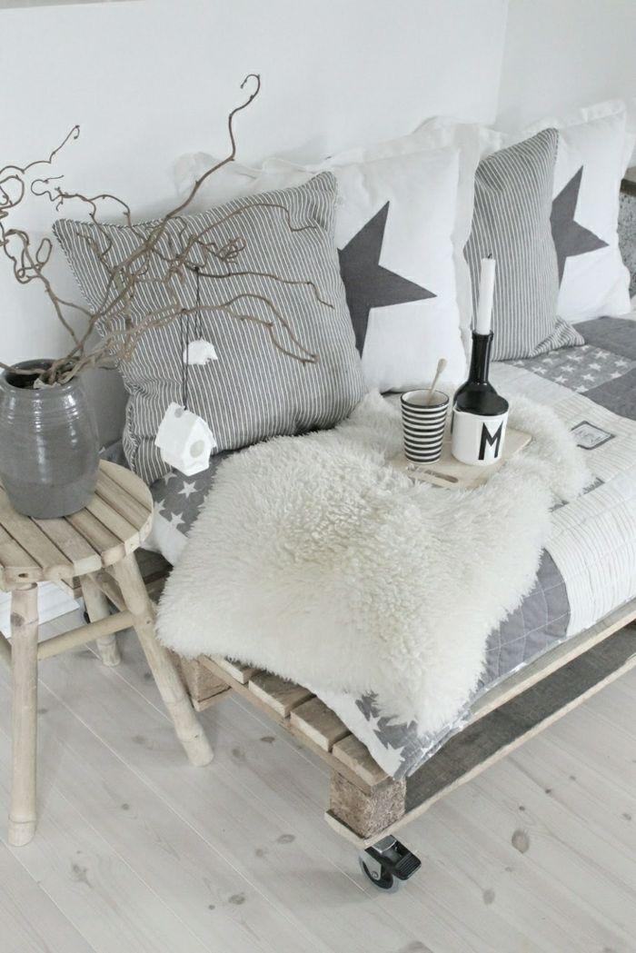 skandinavisches-Interieur-minimalistisch-weiß-grau-Sofa-aus-Paletten-Hocker-Tassen-Topf-Kissen