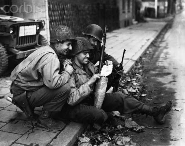 American soldiers laugh at German propaganda leaflets that were fired into German lines on the Siegfried line front. | Location: Schalfenburg, Germany.