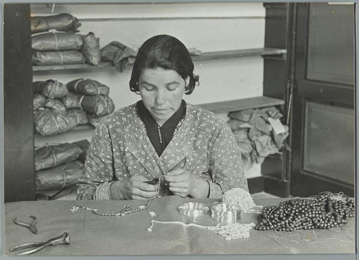 Oude ambachten in St. Willebrord: vrouw aan tafel bezig met het maken van rozenkransen. [1934].