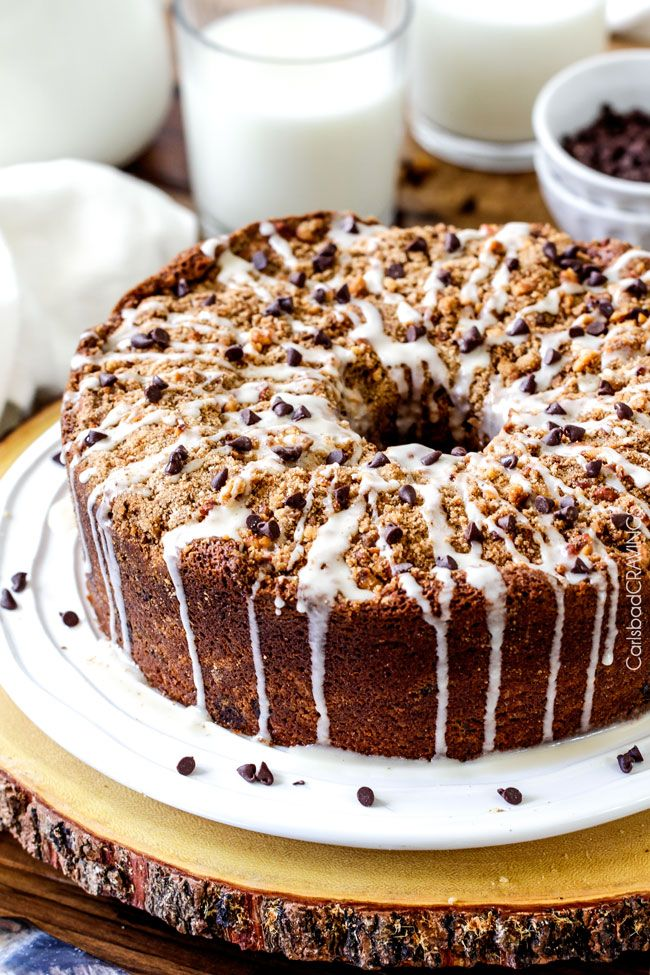 The best Banana ANYTHING ever! Moist Banana Coffee Cake riddled with chocolate chips and walnuts (optional) with an INCREDIBLY creamy cheesecake-like cream cheese filling all topped with brown sugar walnut streusel and vanilla drizzle.
