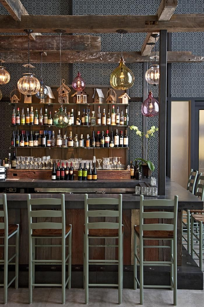 Wall tile and colored glass pendants lend a Moroccan vibe to the front entrance and bar.