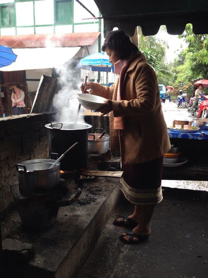 ร้านขายข้าวเปียกในตลาดเช้า แม่ค้านุ่งซิ่น เสื้อสูท ผ้าพันคอ นึกภาพคล้ายครูรัเบียบมายืนลวกเส้น