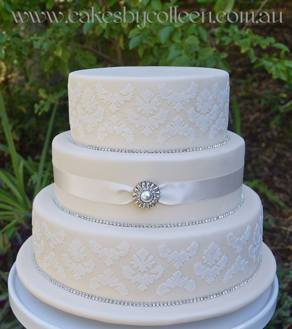 3 Tier ivory embossed wedding cake with diamonte ribbon detail.