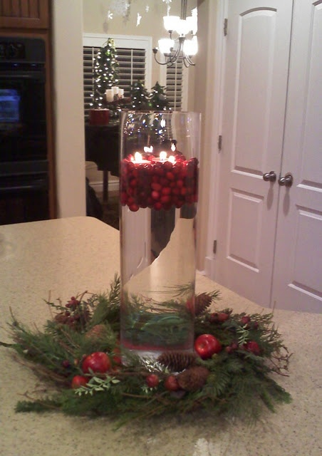 floating cranberries and candles in a tall vase, some greenery at the bottom...would look great in a short, wide one too