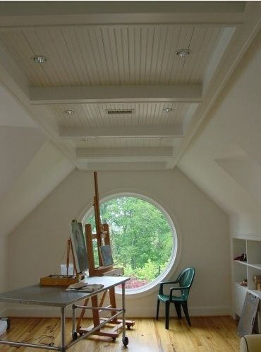 "Creative space ""attic""...love the light that comes through the round window, the built-in book shelves in the wall and the wood beamed ceiling..."