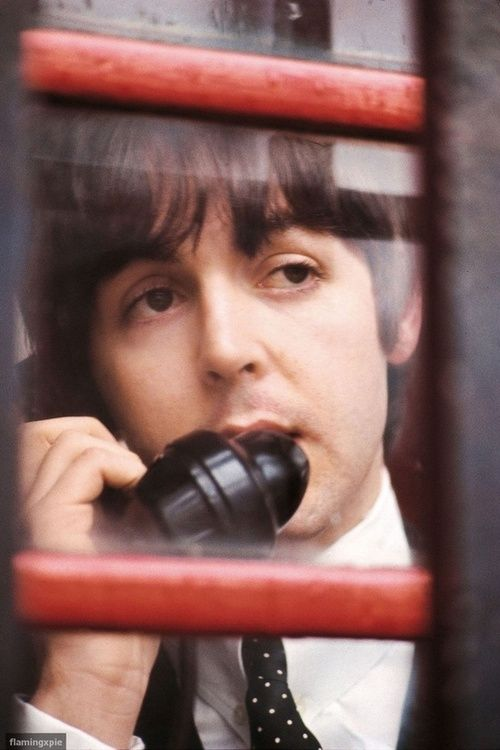 Paul McCartney making a call in a classic red telephone box. dstele.com