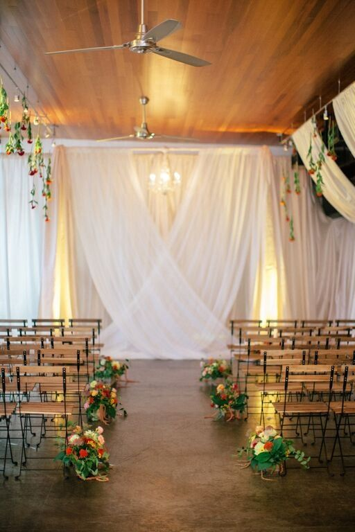 Indoor ceremony backdrop with draped fabric and hanging flowers along the aisle