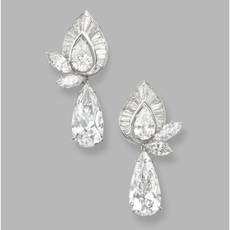 PAIR OF DIAMOND PENDANT-EARCLIPS, HARRY WINSTON. The pear-shaped diamond pendants weighing 5.04 and 5.00 carats, the tops set with pear-shaped diamonds weighing 1.85 carats, marquise-shaped diamonds weighing 1.87 carats, and baguette diamonds weighing 2.13 carats, mounted in platinum, the tops signed Winston, numbered A2109, pendants were custom made for the owner