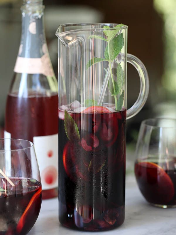 Roasted Cherry Sangria | foodiecrush.com 1 pound cherries, pitted and sliced in half 1 tablespoon sugar 1 750 ml bottle red zinfandel (Gnarly Head) 5 ounces Kirsch (cherry flavored liqueur) 1 orange, thinly sliced 1 750 ml bottle cava brut rosé (sparkling rose wine) mint or basil leaves