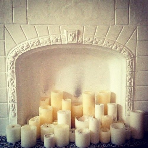 This looks like a great idea for the fireplace....collecting white candles of all shapes and sizes!