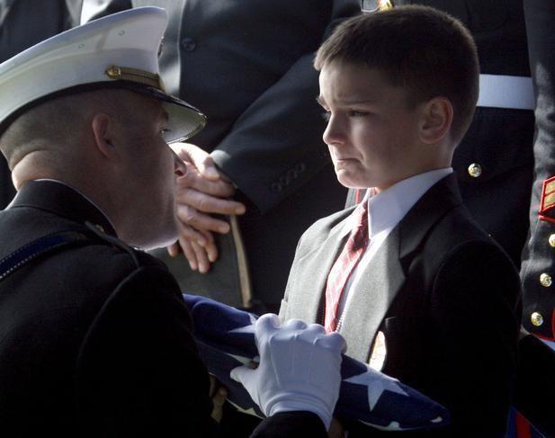 Hijo de un infante de marina caido sostiene la bandera de EE.UU..jpg