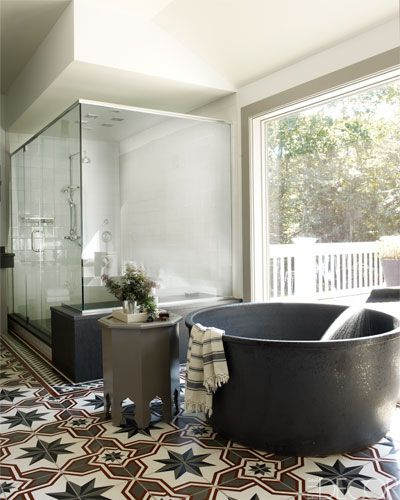 The master bath is paved with handmade cement tiles, and the shower fittings are by Lefroy Brooks.