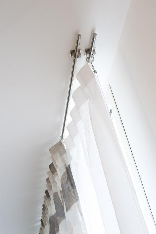 Particolare di bastoni in acciaio di esile diametro posti in opera a soffitto con tende in raso termoimpresso ombreggiante bianco. Realizzato da Tappezzeria Semenzato di Mestre
