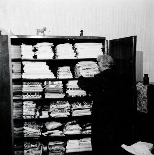 G.A. van der Chijs   Huishouden. Huisvrouw voor goedgevulde linnenkast met stapels lakens, slopen en handdoeken. Nederland, omstreeks 1967. LET OP! Dit is een minimaal bewerkt lowres bestand. Wilt u een groter en/of bewerkt bestand neem dan contact op met 070-3314160 of verkoop@spaarnestadphoto.nl.