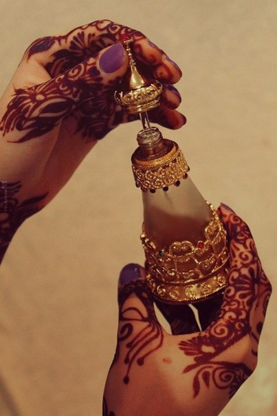 hennaed hands opening a bottle of perfume