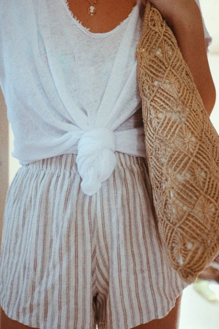 White shirt tied up, flowy shorts with neutral colors and pin stripes and boho woven brown bag