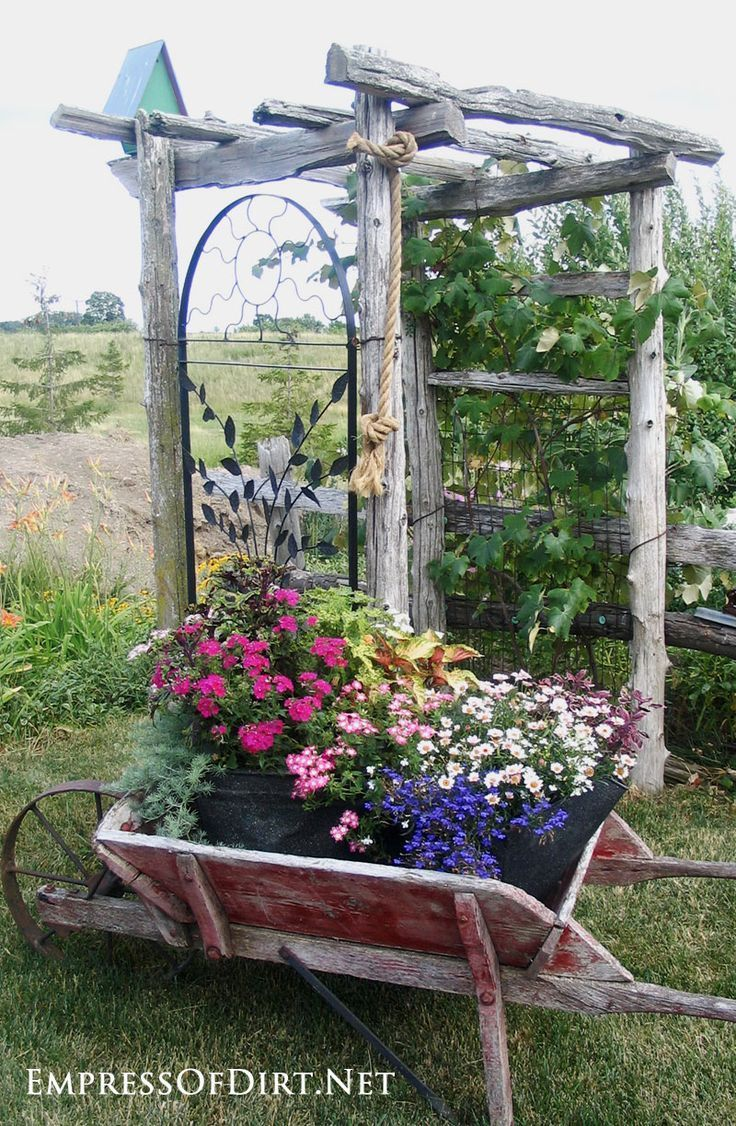 Antique wheelbarrow with flowers by rustic arbor - see 20+ arbor, trellis, and obelisk ideas for your garden