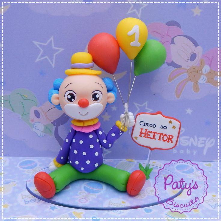 Topo de bolo personalizado palhacinho com balões e placa com nome da criança, para festa temática de Circo. <br> <br>ATENÇÃO!! Antes de encomendar, entre em contato informando seu CEP e data da festa/evento, para consultar disponibilidade na agenda e preço/prazo de frete! <br> <br>Produto sob encomenda. <br>Material: biscuit; base acrílica oval (14x8cm). <br>Altura aproximada: 15cm.