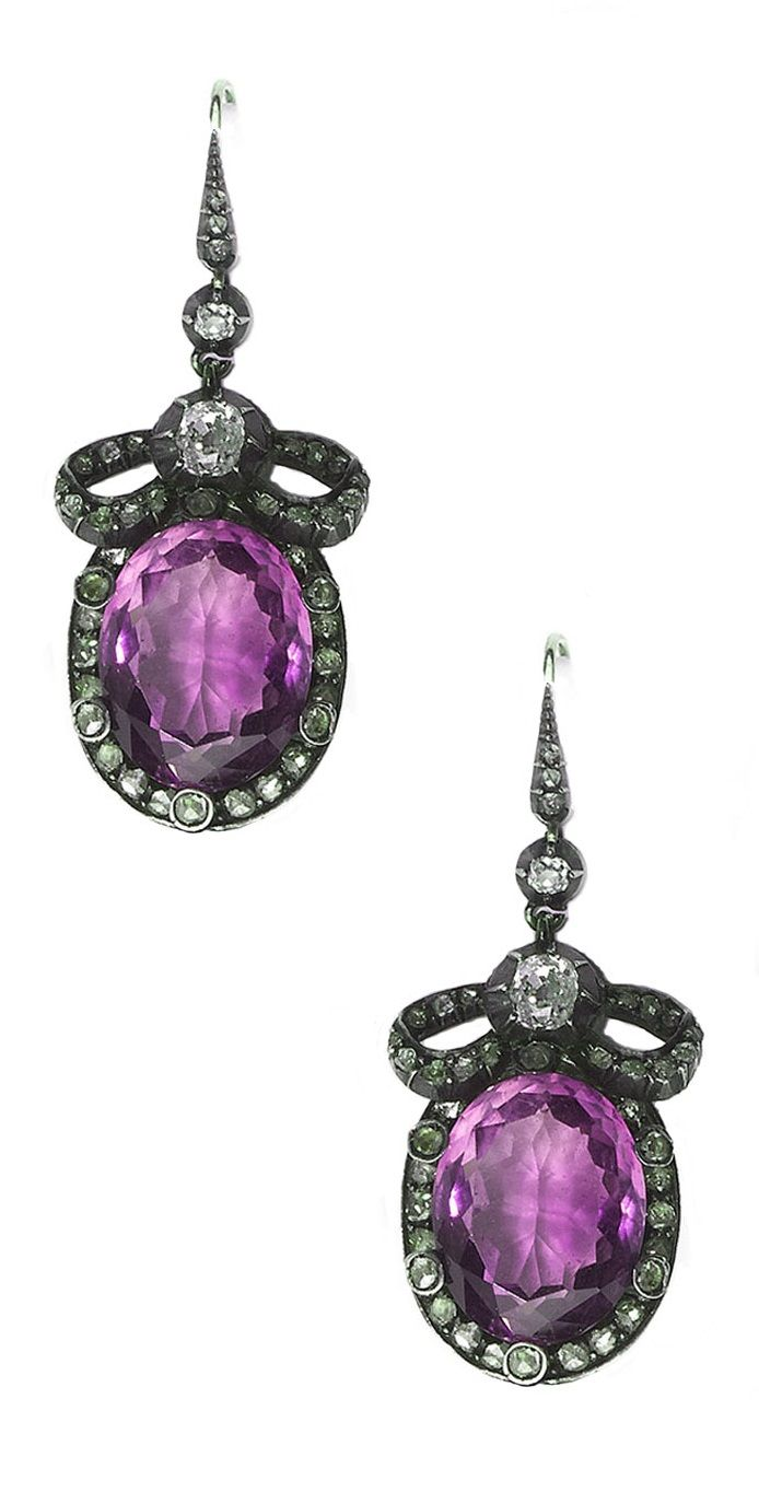 A pair of Victorian amethyst and diamond earrings, circa 1880. Each set with an oval faceted amethyst within a diamond border and bow motif with an old-cut diamond and three further old-cut diamonds above, mounted in silver-upon-gold, on hook fittings.