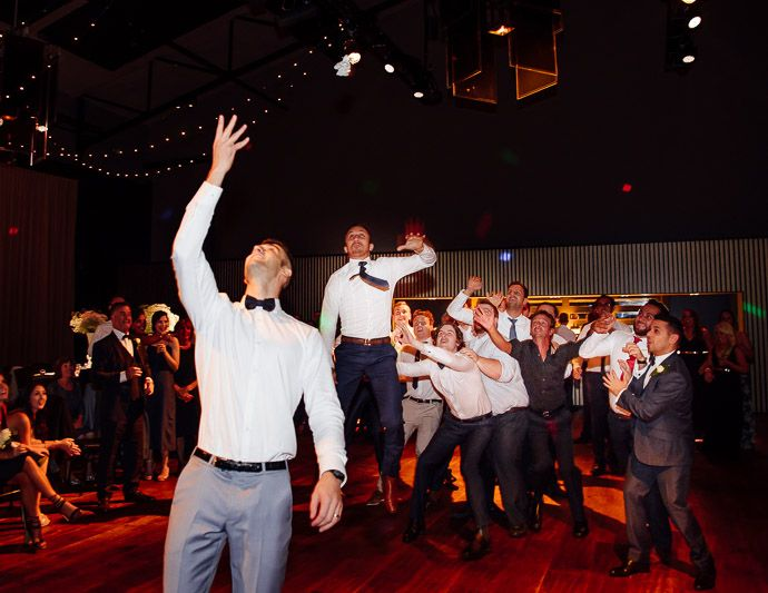 Groom throwing garter at Maia http://www.millgrovephotography.com.au/maia-docklands-wedding-dome-333-collins/