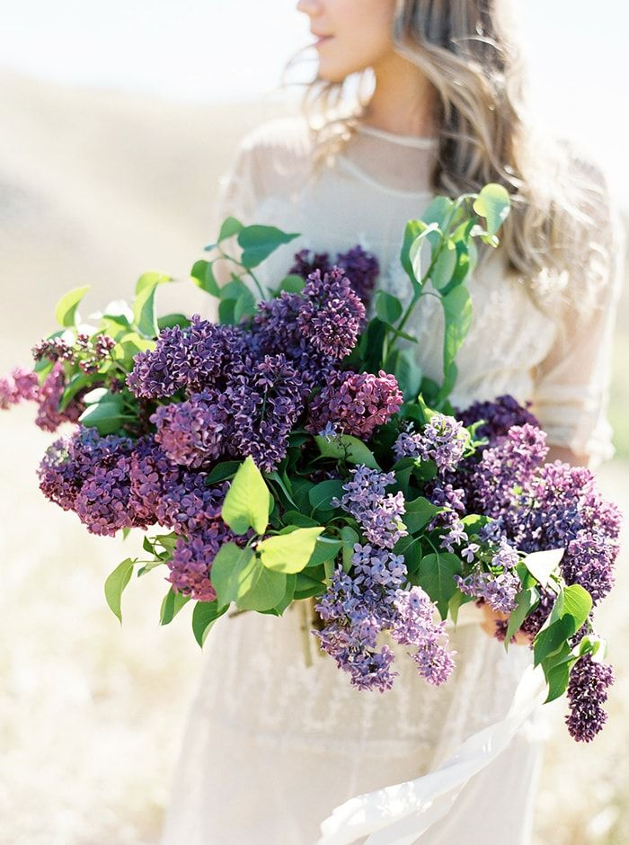 Overflowing lilac bouquet. Bridal portrait with beautiful, glowing light.